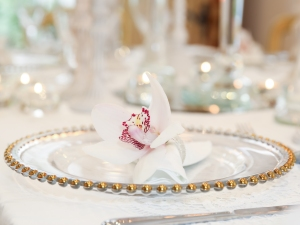 Pretty gold beaded charger plates , crisp white napkins and a single orchid add stylish details to your tablescape.